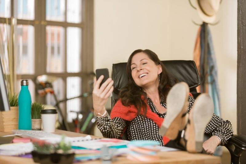 Frau sitz bequem im Chefsessel am Schreibtisch