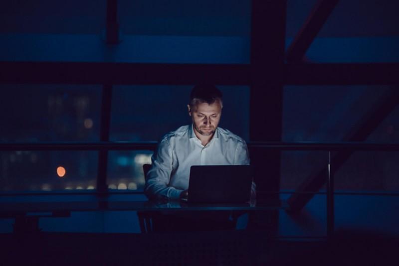 Mann sitzt bei Dunkelheit im Büro und arbeitet an einem Computer
