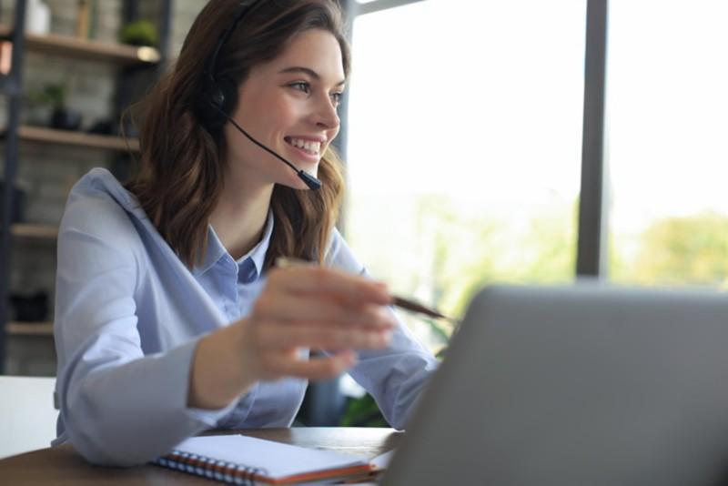 Frau mit Bluetooth Headset vor dem Laptop im Home Office