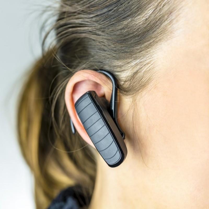 Naheaufnahme von einem Bluetooth Headset mit Bügel direkt am Ohr