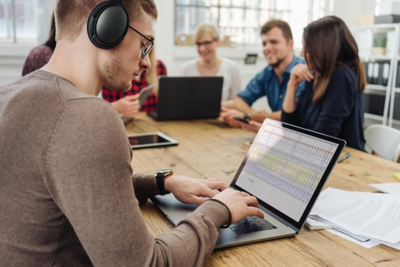 Mann im Büro nutzt ein Headset für Noise Cancelling bei der Arbeit