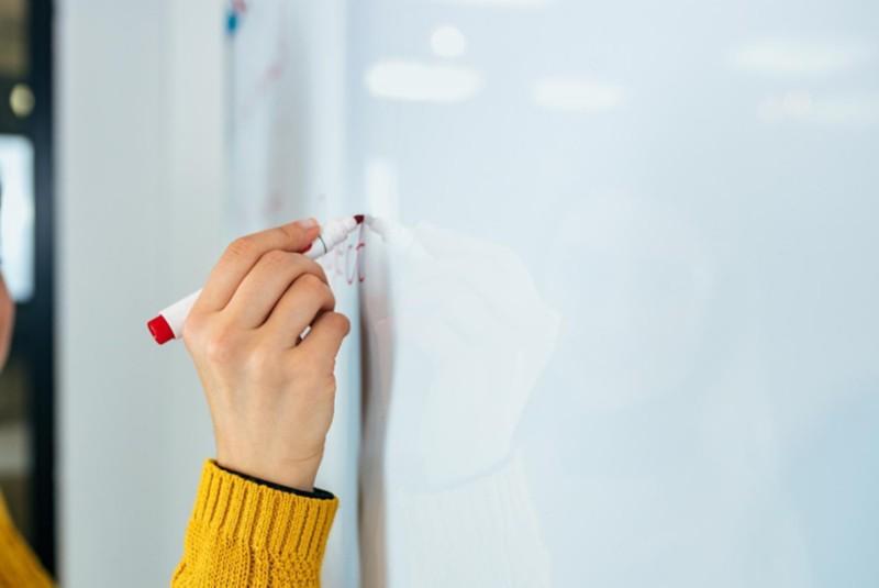Schreiben mit Whiteboard-Stiften auf einem weißen Flipchart