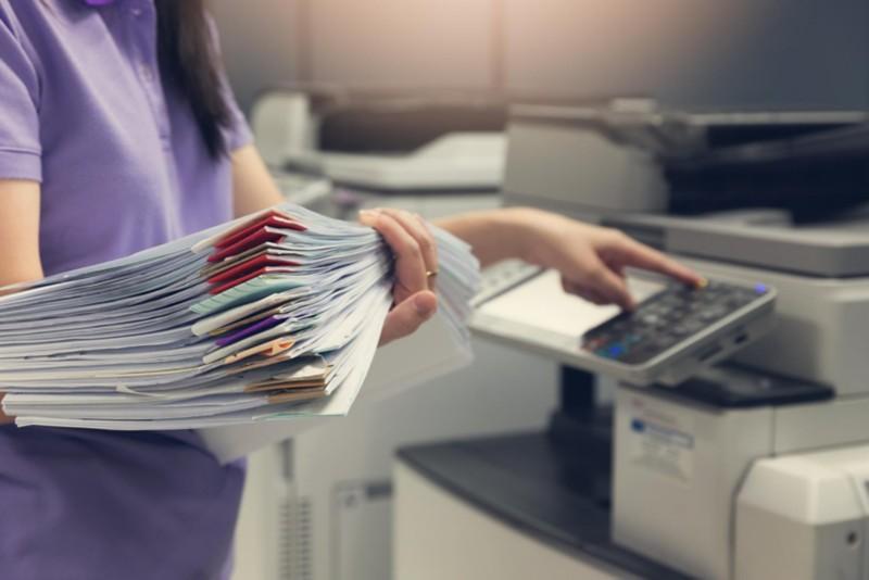 Frau mit Dokumenten an einem Kopiergerät