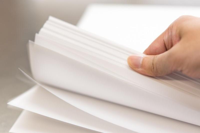 Hand blättert durch Druckerpapier und prüft Oberflächenqualität