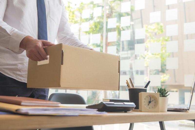 Mann in Anzug stellt Archivbox auf den Schreibtisch