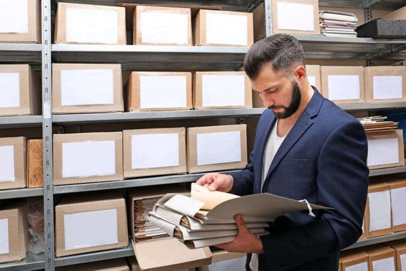 Mann in Anzug durchsucht Akten in Archiv